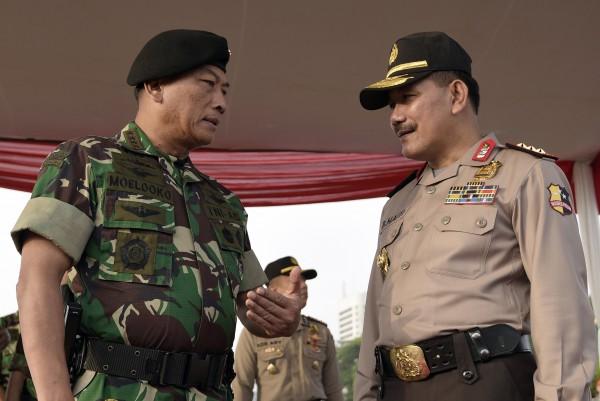 Panglima TNI Jenderal TNI Moeldoko (kiri) berbincang dengan Wakapolri Komjen Pol Badrodin Haiti (kanan) dalam apel gelar pasukan pengamanan KTT Asia-Afrika di Silang Monas, Jakarta, Rabu (15/4).