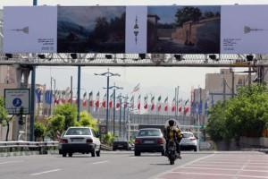 Mobil-mobil melintas di bawah papan iklan yang menampilkan karya seniman lokal dan asing Fotografer: Atta Kenare/AFP/Getty Images