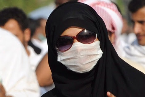 A Muslim pilgrim wears a mask due to fears linked to the MERS virus, as she heads to noon prayers at the Nemra mosque, near Mount Arafat, on October 14, 2013. Some 1.5 million Muslim pilgrims thronged Mount Arafat in Saudi Arabia for the high point of the annual hajj, praying for an end to disputes and bloodshed.  AFP PHOTO/FAYEZ NURELDINEFAYEZ NURELDINE/AFP/Getty Images