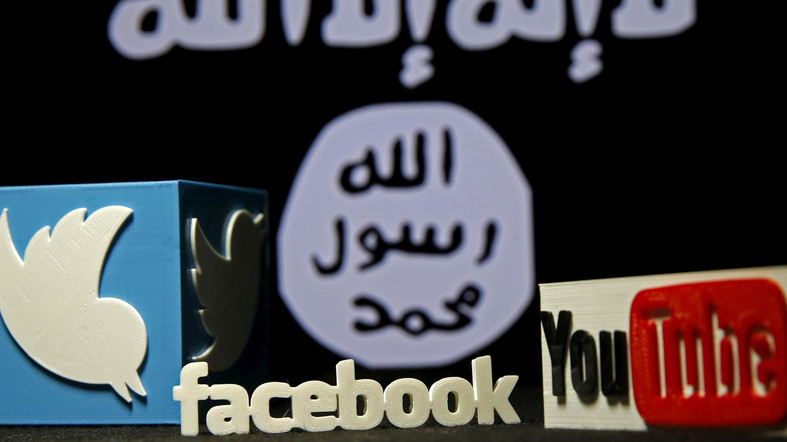 3D plastic representations of the Twitter, Facebook and Youtube logos are seen in front of a displayed ISIS flag in this photo illustration shot February 3, 2016. REUTERS/Dado Ruvic/File Photo - RTX2MYUH