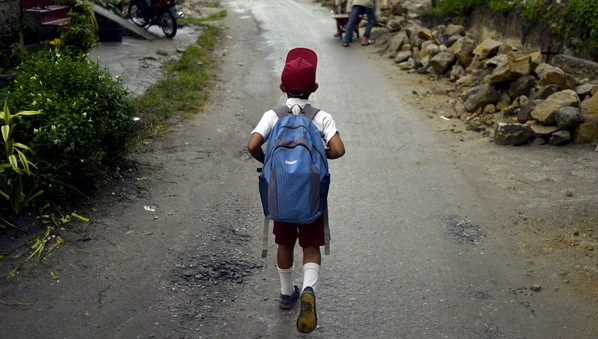 A boy on his way to school on Samosir Island. The island is surrounded by the 5000km2  Lake Toba that formed in the crater of an extinct super volcano. The region is also home to the Toba Batak people.