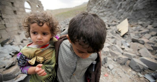 A boy carries his sister over rubble after house was destroyed by a Saudi-led air strike in Sana'a (Image: REUTERS)