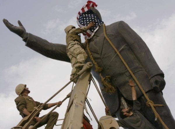 Prajurit Amerika Serikat ketika hendak meruntuhkan patung Saddam Hussein di Irak. Photo: Jerome Delay/Associated Press