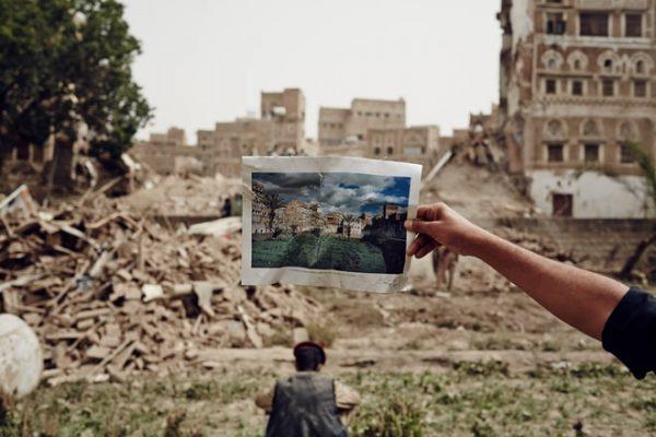 Juli 2015, Sanaa, warga setempat beserta anggota gerakan Houthi membersihkan puing-puing bangunan bersejarah di kota tua yang hancur akibat misil dari pesawat tempur Saudi. Salah seorang Houthi memperlihatkan photo sebelum bangunan tersebut hancur. Photo: Sebastiano Tomada/Getty Reportage