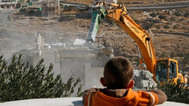 A Palestinian boy looks on as municipality workers demolish a house in the East Jerusalem neighbourhood of Tzur Baher, Tuesday, October 27, 2009. (AP Photo/Dan Balilty)