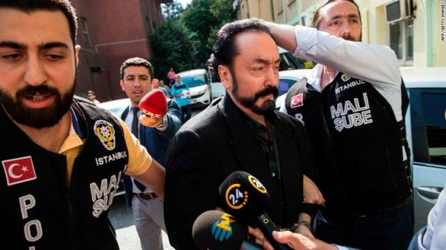 """Turkish police officers escort televangelist and leader of a sect, Adnan Oktar (C) on July 11, 2018, in Istanbul, as he is arrested on fraud charges. - Turkish police detained the televangelist on fraud charges on July 11, 2018, notorious for propagating conservative views while surrounded by scantily-clad women he refers to as his """"kittens"""". (Photo by - / DOGAN NEWS AGENCY / AFP) / Turkey OUT        (Photo credit should read -/AFP/Getty Images)"""